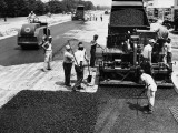 Road Construction Workers Using Machine To Lay New Asphalt on Road