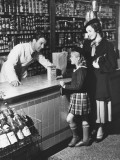 Mother and Daughter (8-9) Standing at Counter  Talking To Shop Assistant