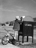 Girl Standing on Tricycle on Suburban Sidewalk  Mailing Letter in Mailbox