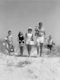 Family of Five  in Bathing Suits  Walking Towards Beach  Carrying Parasol and Picnic