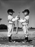 Two Boys in Little League Uniforms  Facing Each Other  Holding Baseball Bat