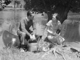 Young Man and Woman Smiling in Front of Canoe With Picnic Basket