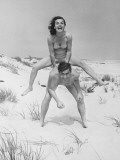 Young Couple on Beach  Woman Leap-Frogging Man  Portrait