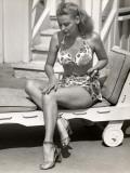Woman Applying Sun Tan Lotion To Her Legs