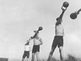 Group of Young Men Exercising Outdoors With Weights
