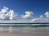 Gentle Waves and Surf Surging onto a Flat Beach under Puffy Clouds