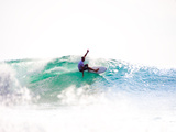 A Surfer Exits the Barrel over a Shallow Reef in Indonesia