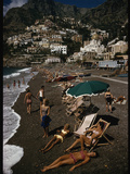 Sunbathers Lounge on a Pebbled Beach by Whitewashed Houses on a Cliff