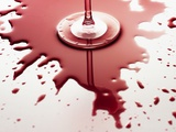 Red wine spilled around glass
