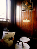 A Man with a Beer Reading a Newspaper in a Pub
