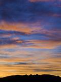 Red and Orange Cumulus Clouds at Sunrise Above Arid Dark Hills