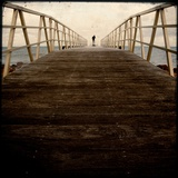 A Long Wooden Walkway at the Sea with a Figure Standing in the Distance