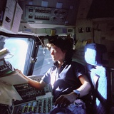 Astronaut Sally Ride Monitors Control Panels from Pilot's Chair of Space Shuttle Challenger