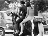 A Naked Young Women and Escort Ride a Horse Through Goose Lake Park at 3 Day Rock Music Festival