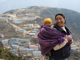 A Woman Carries Her Baby in a Blanket with Namche Visible Behind