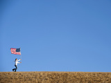 A Teenage Girl Runs across a Field with an American Flag