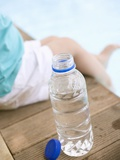 Child Sitting Beside Bottle of Water on Edge of Pool Papier Photo