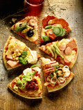 Pieces of Pizza with Different Toppings  on Wooden Background