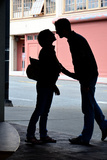 Silhouette of Young Engaged Couple Bending Forward for a Kiss