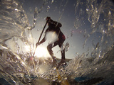 A Stand Up Paddleboarder Surfs a Wave Near Nags Head Pier