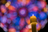A Christmas Candle Glows Against a Rose Window Backdrop