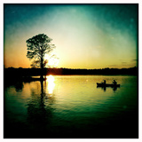 A Couple Paddles a Canoe at Sunset Past Cypress Trees