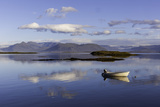 A Johnboat with An Outboard Motor and Its Reflection in Calm Blue Water Papier Photo par Jonathan Irish