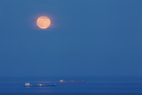 A Full Moon Rising Over Anchored Oil Tankers in Lyme Bay  England