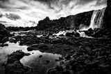 Heavy Clouds Over Oxararfoss Waterfall  and the Rocky Landscape Around It