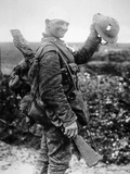 British Soldier with Bandaged Head Shows the Steel Helmet That Saved His Li