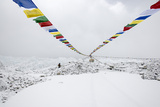 A Porter Walks by a Puja with Prayer Flag in Everest Base Camp  Nepal