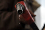 A Pump Attendant Holds a Fuel Nozzle at a Gasoline Station