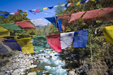 Colorful Prayer Flags Fly over Turquoise Rapids in an Alpine River