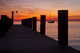 Sunrise on the Water with an Empty Dock and a Sailboat in the Distance of Tilghman Island  Maryland
