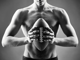 Close-Up of Topless Man Holding Rugby Ball in Isolation