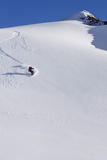 Backcountry Snowboarder Carving Turns Down a Steep Mountain Face