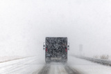 A Delivery Truck Drives During Blizzard Conditions