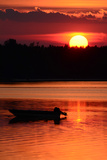 A Silhouetted Boat at Sunset at Cote a Fabien