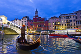 A Gondolier Guides His Boat and Passengers Toward the Rialto Bridge on the Grand Canal at Night