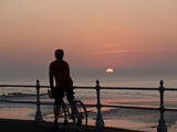 A Cyclist Pauses to Watch the Sunrise  on an Overlook Along the Ocean Front