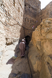 Muslim Men Walking Along a Narrow Mud Brick Alleyway in an Ancient Village in the Desert