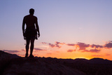 A Climber Watches the Sunset from Atop a Granite Block in Joshua Tree National Park