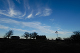Silhouette of Barns and a Windmill Against Blue Sky