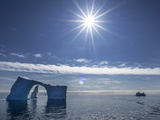 The Bright Sun over a Seascape of Icebergs  One with a Natural Arch in It
