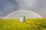 A Double Rainbow  Perfectly Centered over a Grain Silo and Wheat Field after a Thunderstorm Passes
