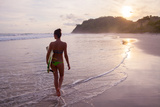 A Young Woman Prepares to Surf on a Beach in Costa Rica