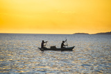 Backlight of Fishermen in a Little Fishing Boat at Sunset
