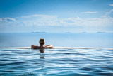 Woman Relaxing in Infinity Swimming Pool on Vacation