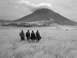 Maasai Warriors Stride across Golden Grass Plains at Foot of Ol Doinyo Lengai, 'Mountain of God' Papier Photo par Nigel Pavitt