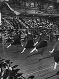 Peppy High School Girl Cheerleaders During their Cheers at the Basketball Game
